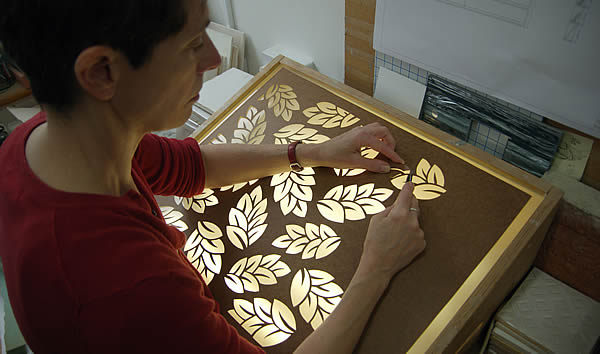 Odette cutting a stencil for a new leaf design