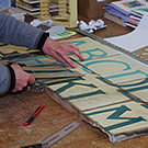 Painting the letters onto the glazed tiles